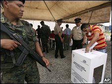 A soldier guards a polling station at a prison in Guayaquil, Ecuador, while an inmate votes on Friday