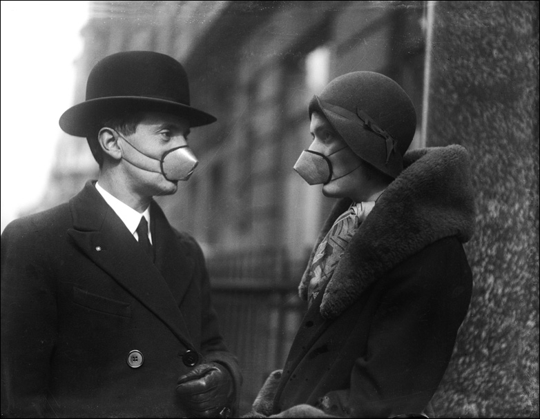 A man and a woman wearing anti-flu masks