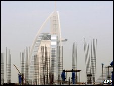 Construction workers in front of Dubai's landmark Burj al-Arab hotel