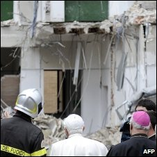 The Pope talks to a fire brigade chief as he visits the student dormitory in L'Aquila destroyed by the quake on 6 April