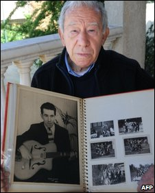 Auschwitz survivor Albert Veissid posing with picture album