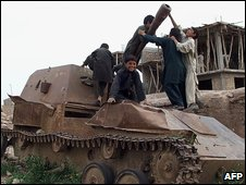 Afghan children play on a Russian tank in Herat