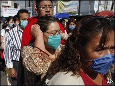 People wearing surgical masks stand in line in Mexico City