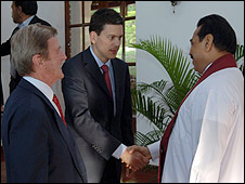 David Miliband shakes hands with President Rajapaksa watched by Bernard Kouchner