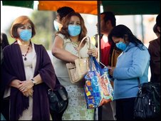 People wear surgical masks, to help prevent being infected with the swine flu, as they wait for a public bus on April 29, 2009 in Mexico City