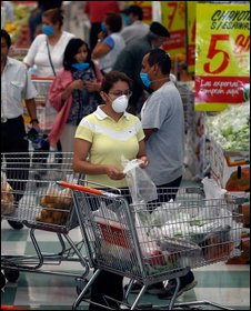 People wear surgical masks to help prevent being infected with the swine flu as they shop in a grocery store on 29 April 2009 in Mexico City