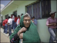 People stand outside the house of a child who has reportedly survived swine flu in La Gloria, Mexico