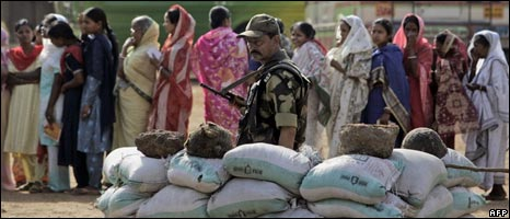 A soldier stands guard as voters queue up at a polling station in Lalgarh in West Bengal on April 30, 2009