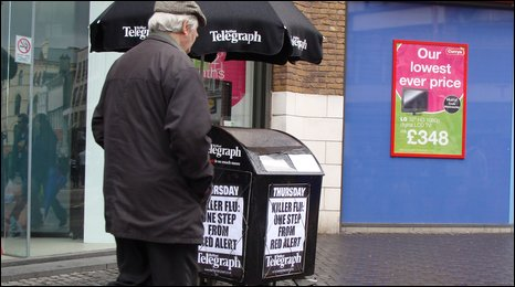 Man walking past newspaper stand