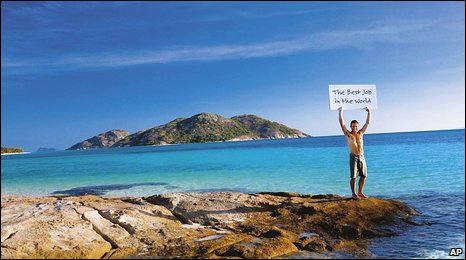 Tourism Queensland picture, a man stands on rocks  with 'best job' sign