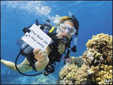 Queensland tourism board picture with woman diver holding Best Job sign