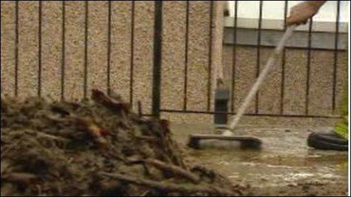 Man sweeps up flood debris