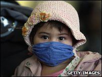 A young girl poses for photographers with a mask bought from Mexico after departing a flight from Mexico City at Gatwick Airport