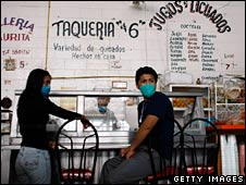 Masked customers at a take-away food stall in Mexico City on 30 April 2009