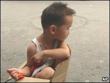 young child sits in a cardboard box on the edge of a road in Beijing
