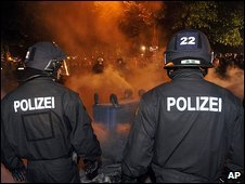 German police look on at burning dustbins after clashes in Berlin on 1/5/09