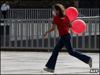 A girl wears a mask as she runs with balloons