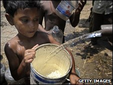 A young boy collects water from a tanker in South Asia (file picture)