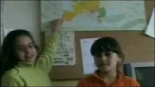 Two school girls pointing towards a map: Video grab, Charline Evans