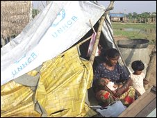 A woman feeds her baby as she rests in her makeshift tent Thursday, April 30, 2009, in Twantay