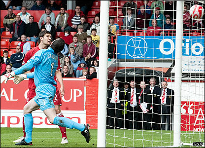 Andy Considine heads over his own keeper