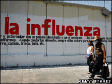 People pass a sign warning of flu symptoms in Mexico City, 1 May