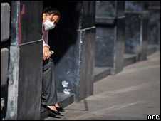 A woman wearing a mask sits in a doorway in Mexico City on 3 May 2009
