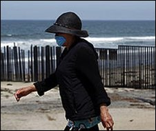 Woman wearing a mask walks on the beach near the US-Mexico border in Tijuana, Mexico, on 3/5/09