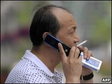A man talks on a mobile phone while smoking cigarettes along a street in Beijing