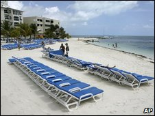 Few tourists enjoy a nearly empty beach in the resort city of Cancun, Mexico, Friday, May 1, 2009.