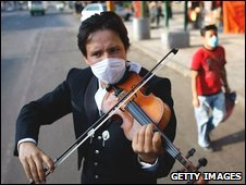 Mariachi player, Gabriel Navarro, wears a surgical mask, to help prevent being infected with the swine flu, as he plays his violin on April 28, 2009
