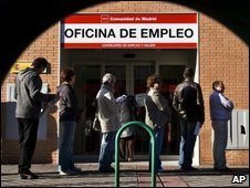 People queue outside a government job centre in Madrid