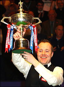 2009 champion John Higgins holds aloft his trophy