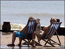 Sunbathers on a beach (Photo: John Stillwell/PA)