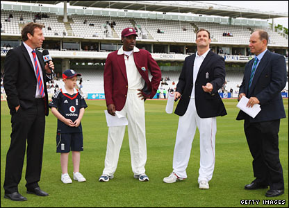 England captain Andrew Strauss tosses the coin, watched by opposite number Chris Gayle, television commentator Mike Atherton, match referee Andy Pycroft and England's young mascot