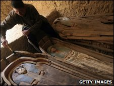 An Egyptian brushes a wooden coffin containing a linen-wrapped mummy in Lahun's pyramid field