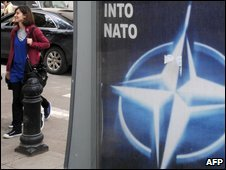 A woman passes a Nato poster in Tbilisi, 6 May