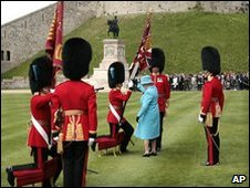 The Queen presenting the colours to two  guards