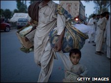 A refugee holds his son's hand as they flee fighting in Buner, Pakistan, 6 May