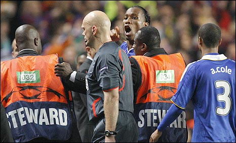 Chelsea striker Didier Drogba confronts ref Tom Henning Ovrebo after his side are knocked out of the Champions League by Barcelona