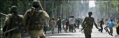 Indian paramilitary soldiers chase Kashmiri protesters in Srinagar on 7 May 2009