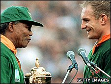 Former South African leader Nelson Mandela presents captain Francois Pienaar with the World Cup trophy in 1995