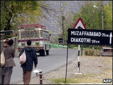 Kashmiri villagers walk past a road sign showing the distance to Muzaffarabad