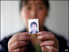 Huang Fumei, 41, holds a picture of her son Shuangshuang who was killed on 12 May