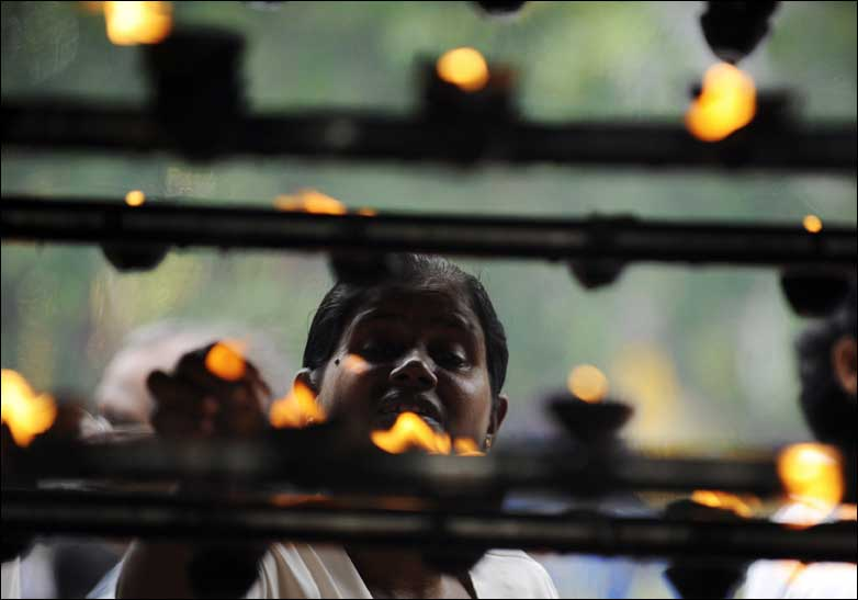 Sri Lankan Buddhists light oil lamps