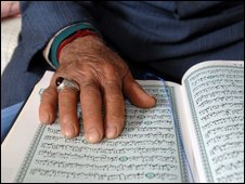 A man reads a copy of the Qur'an