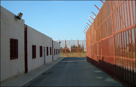 Exterior of the camp, with large orange fence to right and building to left