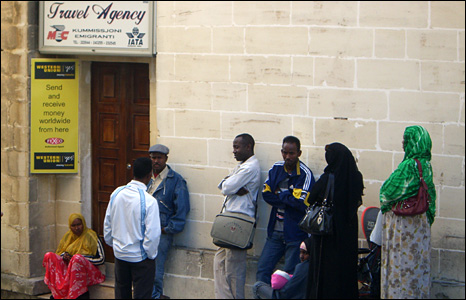 Asylum seekers queuing outside a travel agency in Valletta