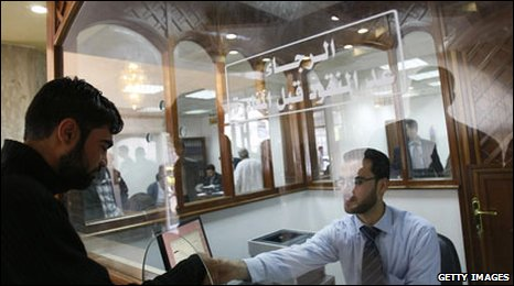 A Palestinian bank clerk serves a customer