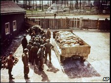US troops stand near a lorry piled with bodies at Buchenwald, 11 April 1945